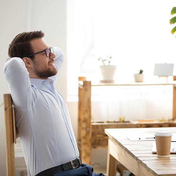 Relaxed man sitting holding hands behind head indoors