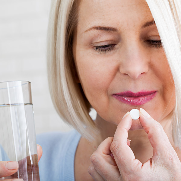 Doubtful sick ill middle woman holding pill and glass of water taking painkiller medicine drugs to relieve headache pain, worried about side effects of antidepressant or emergency contraceptive meds